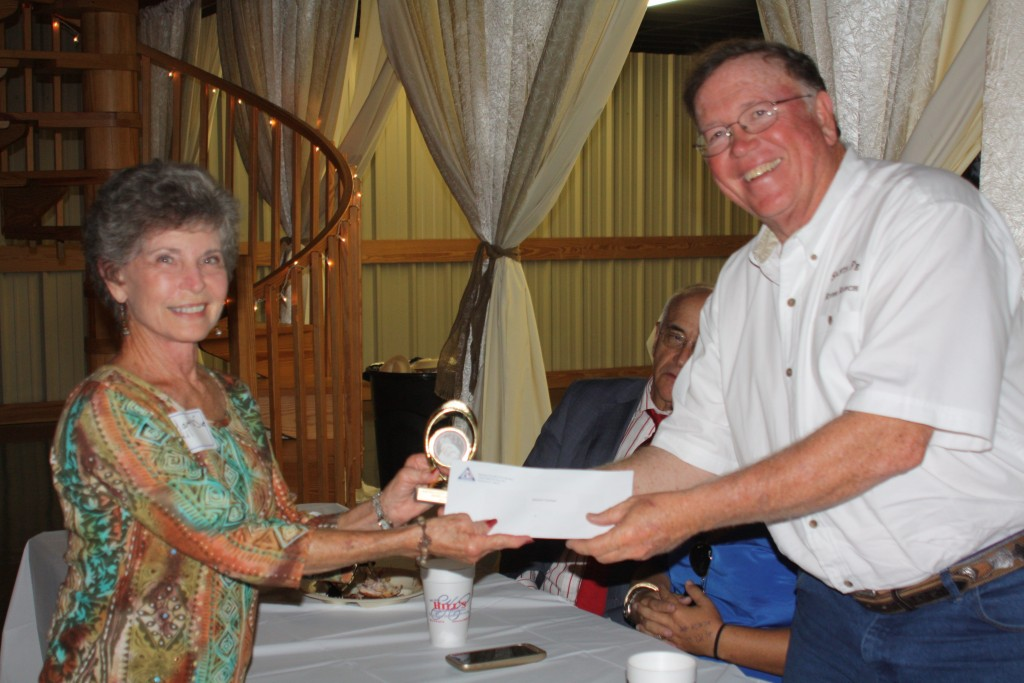 Martha Sue Hill accepts a check and trophy for her outstanding dessert from Alan Hitchcock, ACFB treasurer and proprietor of Santa Fe River Ranch.
